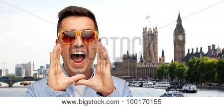 travel, tourism, emotions, communication and people concept - face of angry middle aged latin man in shirt and sunglasses shouting london city background