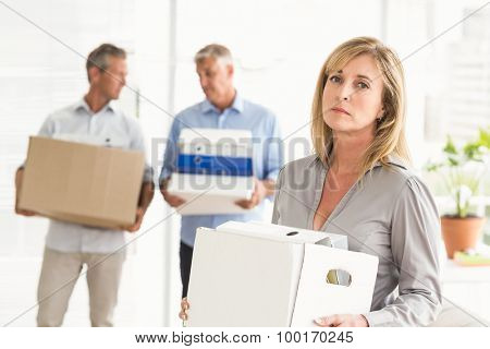 Portrait of disappointed casual businesswoman with carton in the office