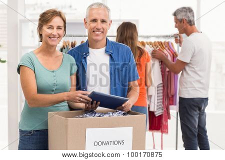 Portrait of smiling casual business colleagues with donation box in the office