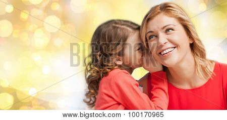 people, family, holidays, christmas and holidays concept - happy mother and daughter whispering something into ear over yellow lights background