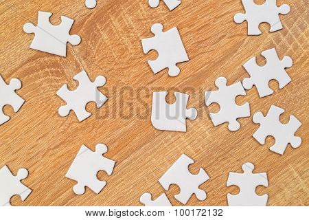 White Jigsaw Puzzle Pieces Scattered On Wooden Table