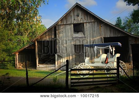 Old barn and a antique horse buggy with a fringe on top