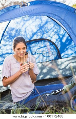 Brunette camper with cup sitting in tent in the nature