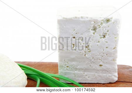 diet food : greek feta white cheese served on small wooden plate isolated over white background