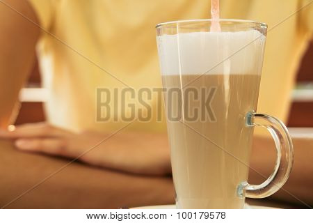 Woman Sits At A Table In A Cafe And Drinking Latte In A Glass With Straw Closeup