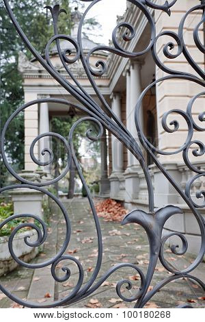 Wrought gate and big neoclassical house background