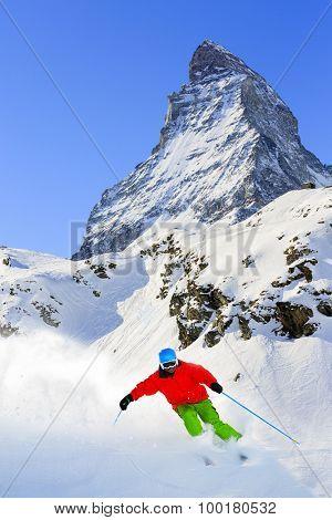 Skiing, Skier, Freeski, Freeride in Zermatt - man skiing downhill in fresh powder snow