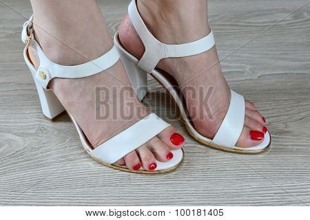Women's legs and white sandals