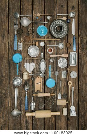 Vintage decoration of ancient kitchen equipment with cutlery and dishes on old wooden background for gastronomy.