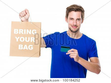 Man with shopping bag and credit card for showing phrase bring your bag