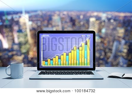 Laptop With Business Graph On A Table In Evening Office