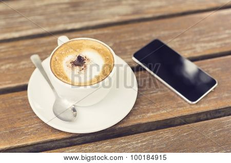 Cappuccino With A Teaspoon And A Cell Phone
