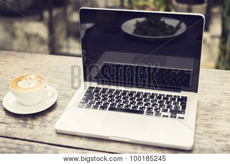 Laptop And Cup Of Cappuccino On A Wooden Table