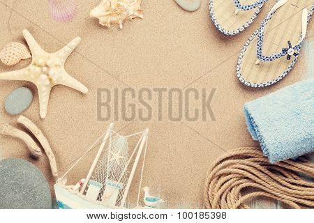 Travel and vacation items on sea sand. Top view with copy space. Toned