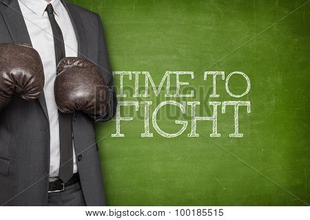 Time to fight on blackboard with businessman on side
