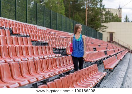 Woman With A Bottle At The Stadium