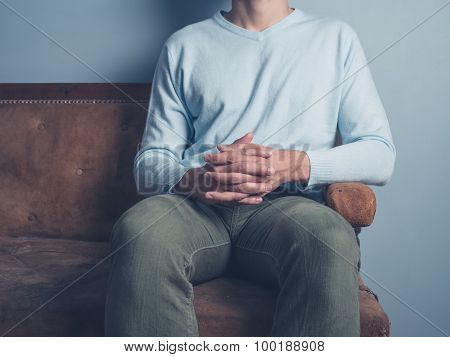 Young Man Sitting On Sofa With Hands Folded