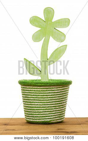 Spring basket with wooden decorative flower on the wooden background.