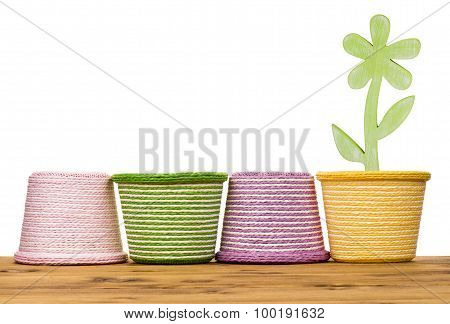Spring baskets with wooden decorative flower on the wooden background.