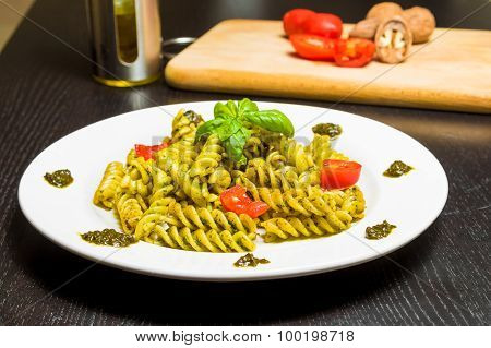 Dish Of Pasta With Pesto Genovese Sauce And Vegetables, Tomato And Basil On Black Wood Table