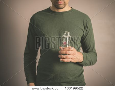 Young Man Holding A Small Glass Bottle