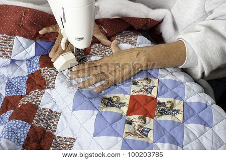 A Quilter Machine Quilting Patriotic Quilt.