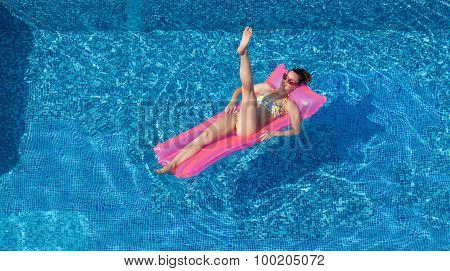 Sexy Brunette Woman Doing Gymnastic Exercise On Inflatable Mattress In Pool