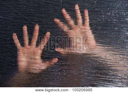 Male hands behind frosted glass, close-up