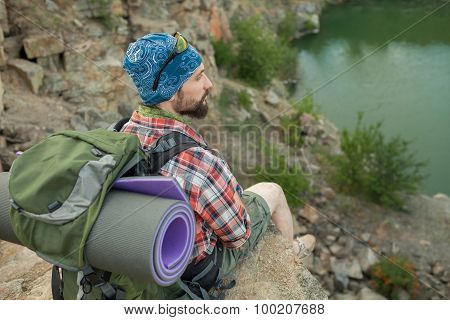 Young caucasian man with backpack sitting on the top of hill