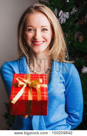 Laughing woman giving red gift