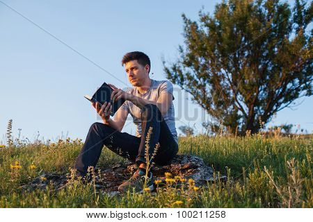 Man Sits On A Hill With A Book And Looking Away