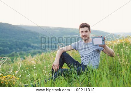 Man Sits On The Hill And Hold In One Hand An Ebook