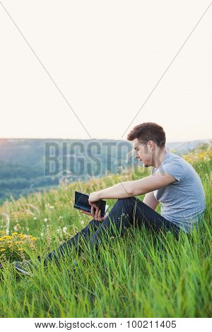 Man Sitting On The Hill And Reading A Book Vertical