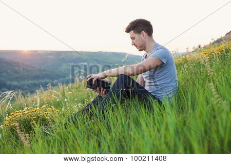 Man Sits On The Hill And Reading A Book