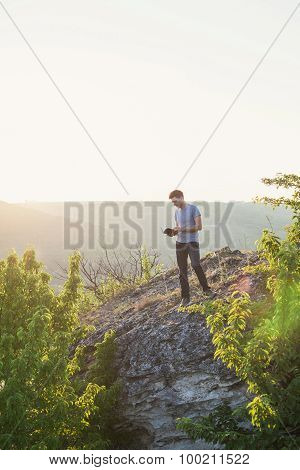 Man Stands On A Hill And Reading A Book Vertical