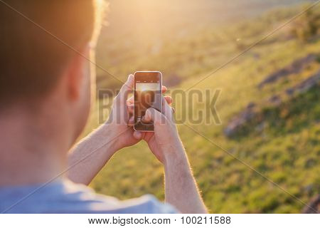 Man Takes A Picture Of Sunset
