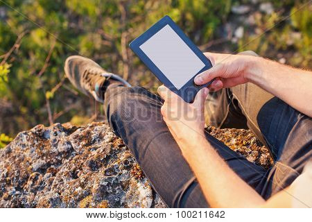 Men's Hands Hold An Ebook On The Edge Of Cliff