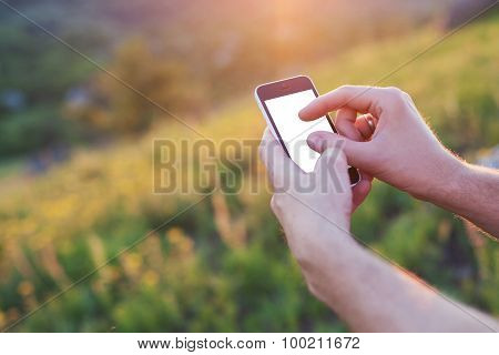 Men's Hands Hold The Phone And Touch The Screen