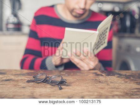 Man Reading Book In Kitchen