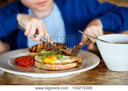 Boy eating fried egg on toast and porridge for breakfast