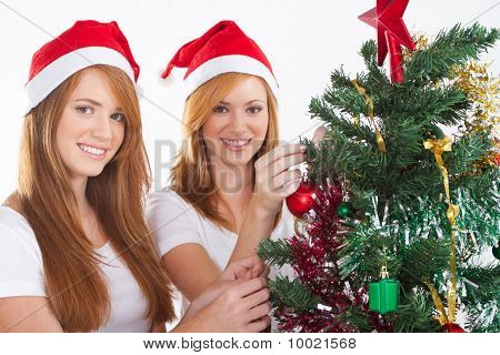 young sisters decorating christmas tree