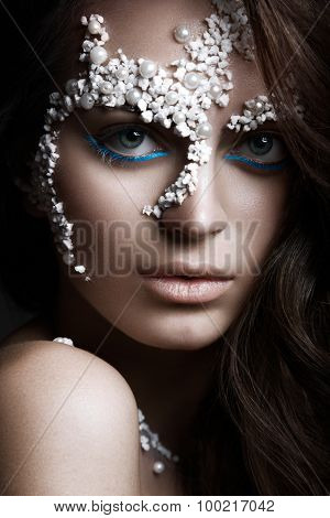 Beautiful dark-haired girl with a fashionable creative makeup. Beauty face. Art image.