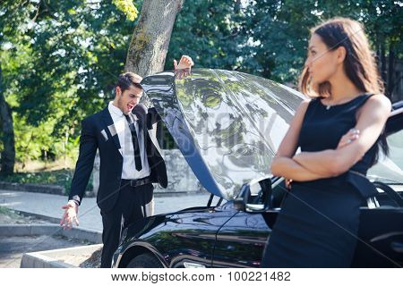 Man looking at open hood in broken car