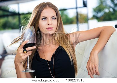 Beautiful young woman sitting at the restaurant with glass of red wine