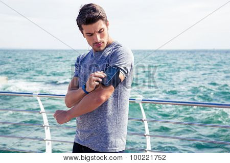 Handsome male runner listening to music adjusting settings on armband for smartphone outdoors