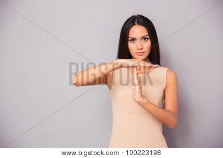 Beautiful woman showing time out sign over gray background