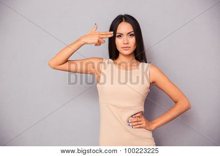 Portrait of a beautiful young girl making gun gesture to her head over gray background