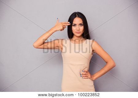 Portrait of a pretty woman making gun gesture to her head over gray background
