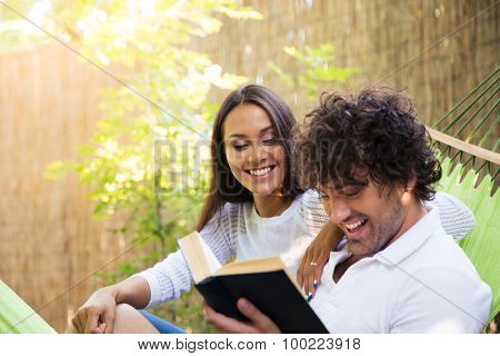 Happy couple reading book on hammok outdoors