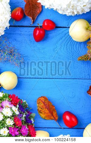 Apples, flowers, leaf litters and plums on a blue table